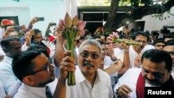 Gotabhaya Rajapaksa (C), former defense secretary and brother of Sri Lanka's ex-president Mahinda Rajapaksa, holds the symbol of the Sri Lanka People's Front, at a party event in Colombo, Sri Lanka, July 4, 2018.