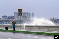 FILE - A jogger makes his way along Bayshore Blvd., in Tampa, Fla. as a wave breaks over a seawall, during the aftermath of Tropical Storm Elsa, July 7, 2021.
