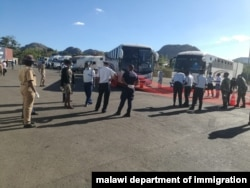 Immigration officers at Mwanza border wellcoming buses carrying Malawi returnees. (Courtesy: Pasqually Zulu/Immigration Department)