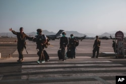 A US Marine escorts US Department of State personnel to be processed for evacuation at Hamid Karzai International Airport, in Kabul, Afghanistan, Aug. 15, 2021. (US Marine Corps photo)