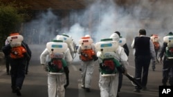 Firefighters disinfect a square against the coronavirus, in western Tehran, Iran, March 13, 2020.
