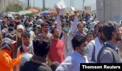 资料照片:人们聚集在喀布尔机场外向美国军人展示着文件。