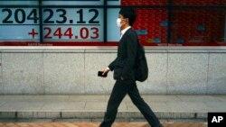 ຊາຍຄົນນຶ່ງໃສ່ຜ້າປິດປາກ ຍ່າງຜ່ານກະດານຂ່າວ ກ່ຽວກັບ ດັດຊະນີຮຸ້ນ Nikkei 225 ຂອງຍີ່ປຸ່ນ ຢູ່ບໍລິສັດຂາຍຮຸ້ນ ໃນນະຄອນໂຕກຽວ (ວັນທີ 11 ພຶດສະພາ, 2020)