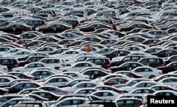 FILE - A worker walks along rows of Mercedes-Benz cars at a shipping terminal in the harbor of the town of Bremerhaven, Germany, March 8, 2012.
