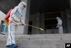 Staf Sekolah Dasar Pyongyang No 4 melakukan penyemprotan disinfektan di Pyongyang, Korea Utara, Rabu, 30 Juni 2021.