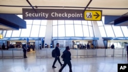 FILE - Sign points to a Transportation Security Administration (TSA) checkpoint at Dulles International Airport in Dulles, Va., March 26, 2019.