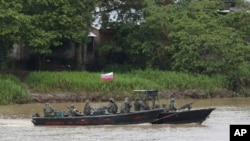 Soldados de la Armada venezolana patrullan el río Arauca, la frontera natural con Colombia, visto desde Arauquita, Colombia, el 26 de marzo de 2021.
