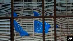 """European Union flags are reflected in a window of the European Council in Brussels, Dec. 19, 2020. The European Union and the United Kingdom were making a """"last attempt"""" to clinch a post-Brexit trade deal Saturday."""