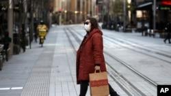 Seorang wanita melintasi jalan yang biasanya ramai di Sydney, Rabu, 7 Juli 2021. (Foto: AP)