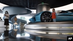 A child pose for photos near a race car displayed at the NIO flagship store in Beijing on Thursday, Aug. 20, 2020. The chairman of Chinese electric car brand NIO says it plans to start expanding to Western markets next year. William Li said the…