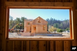 In this Nov. 4, 2019, photo, members of the Chandler family, father Joel and sons Bobbie and Dale, and their construction crew build a home in Calistoga, Calif.