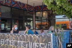 Patrons observing social distancing rules sit outdoors at the Guerrilla Tacos restaurant in Los Angeles, July 3, 2020.