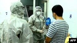 Các bác sĩ khám chữa cho hai bệnh nhân dương tính với virus corona tại khu cách ly của bệnh viện Chợ Rẫy, Thành phố Hồ Chí Minh, ngày 23/1/2020 (AFP)