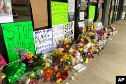 A makeshift memorial is seen March 19, 2021, in Acworth, Ga., in the aftermath of shootings that left eight people dead at three metro Atlanta massage businesses.