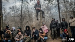 TOPSHOT - Migrants sit waiting near the buffer zone at Turkey-Greece border, at Pazarkule, in Edirne district, on February 29, 2020. - Thousands of migrants stuck on the Turkey-Greece border clashed with Greek police on February 29, 2020, according…