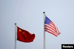 FILE - Chinese and U.S. flags flutter outside a company building in Shanghai, China April 14, 2021.