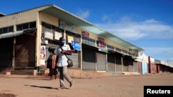 FILE - A man wears a mask as he walks past closed shops during a lockdown aimed at limiting the spread of the coronavirus disease (COVID-19) in Harare, Zimbabwe, Jan. 28, 2021.