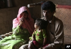 FILE - Pakistan's Tariq Ali, 30 along with his wife Parveen and three-year-old Ume Kulssom all infected with HIV sit at their home in a village near Ratodero, May,16, 2019.