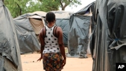 File - A woman who said she was trafficked from Nigeria under false pretenses to work as a sex slave in Burkina Faso's mining sites, walks through a row of tent in the Secaco mining town June 12, 2020.