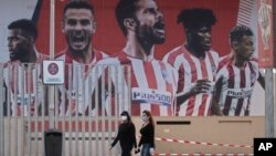 Two women wearing face masks pass by a giant poster of Atletico Madrid soccer players at the Wanda Metropolitano stadium in Madrid, Spain, May 5, 2020.