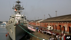 File - Indian school children walk past the visiting Indian Navy warship INS Kirch for a guided tour in Kolkata, Dec. 5, 2019. India is sending four navy ships for exercises and port visits in the Indo-Pacific region as China's maritime power grows.