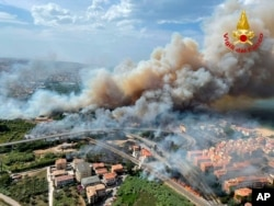 In this photo released by the Italian Firefighters, a view of a violent wildfire that burned the historical pinewood in Pescara, central Italy, Aug. 1, 2021.