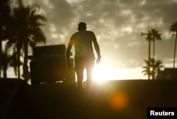 A man makes his way up a hill following his morning beach workout in California, America's largest state, which experienced the lowest growth rate in its history between 2010 and 2020.