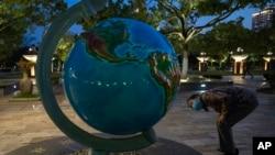 Чоловік у китайському місті Ухань дивиться на величезний глобус