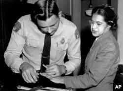 Dalam foto pada 22 Februari 1956 ini, Rosa Parks diambil sidik jarinya oleh polisi Letnan D.H. Lackey di Montgomery, Alabama, setelah menolak menyerahkan kursinya di bus untuk penumpang kulit putih pada 1 Desember 1955.