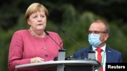 The Major of Templin looks on as German Chancellor Angela Merkel speaks during the 750th city anniversary celebrations in Burgergarten, in Templin, Germany, Sept. 10, 2021.