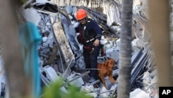 Fire rescue personnel conduct a search and rescue with dogs through the rubble of the Champlain Towers South Condo after the multistory building partially collapsed in Surfside, Fla., June 24, 2021.