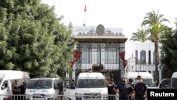 Police officers stand guard outside the parliament building in Tunis, Tunisia, July 27, 2021.