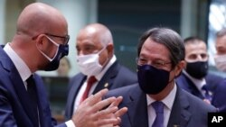 European Council President Charles Michel, left, speaks with Cypriot President Nicos Anastasiades during a round table meeting at an EU summit at the European Council building in Brussels, Oct. 1, 2020.
