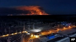 In this photo taken from the roof of Ukraine's Chernobyl nuclear power plant late Friday April 10, 2020, a forest fire is seen burning near the plant inside the exclusion zone. Ukrainian firefighters are labouring to put out two forest blazes in…