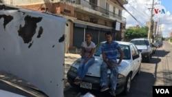 """Antonieta y Mervis, de 24 y 30 años, esperan en una larga fila de vehículos a las afueras de una estación de servicio en Maracaibo. Dicen que no votaron porque la elección de hoy es """"una trampa""""."""