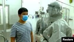Thứ trưởng Y tế Nguyễn Trường Sơn nói chuyện với một bệnh nhân trong khu cách ly của một bệnh viện tại TPHCM.