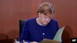 ນາຍົກລັດຖະມົນຕີ Angela Merkel ຂອງເຢຍຣະມັນ ອ່ານເອກະສານ ພາຍຫລັງທີ່ໄປເຖິງຫ້ອງປະຊຸມຄະນະລັດຖະບານປະຈຳອາທິດ ຢູ່ສຳນັກງານນາຍົກ ໃນນະຄອນຫລວງເບລິນ ຂອງເຢຍຣະມັນ, ວັນທີ 8 ມັງກອນ, 2020