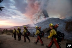 FILE - Firefighters walk in line during a wildfire in Yucaipa, Calif., Sept. 5, 2020. Three wildfires sent people fleeing, with one trapping campers in the Sierra National Forest, as a heat wave pushed temperatures into triple digits.