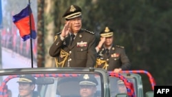 FILE - Cambodian Prime Minister Hun Sen (L) salutes, along with his son, Lt. Gen. Hun Manet (background) during an inspection of troops at a ceremony in Phnom Penh, Cambodia, Jan. 24, 2019. (Handout via AFP)