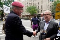 미국 뉴욕 시장 예비선거에 출마한 공화당 커티스 실와 후보(왼쪽)와 민주당 스캇 스트링어 후보가 22일 거리유세 도중 악수하고 있다.