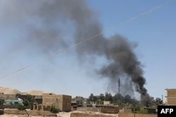 FILE - A plume of smoke rises amid ongoing fighting between Afghan security forces and Taliban insurgeents in the western city of Qala-e-Naw, the capital of Afghanistan's Badghis province, July 7, 2021.