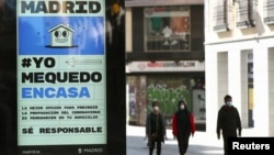 An billboard advising people to be responsible and stay home is seen at the almost empty Preciados Street, due to the coronavirus outbreak, in central Madrid, Spain, March 14, 2020.