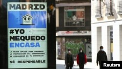 A billboard advising people to be responsible and stay home is seen at the almost empty Preciados Street, due to the coronavirus outbreak, in central Madrid, Spain, March 14, 2020.