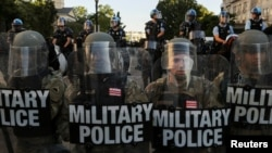 FILE - DC National Guard Military Police officers and law enforcement officers stand guard during a protests against the death in Minneapolis custody of George Floyd, near the White House in Washington, June 1, 2020.