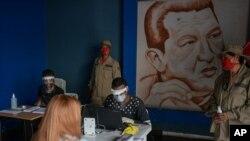 Miembros del Consejo Electoral venezolano, con tapabocas y escudos protectores, verifican la autenticidad de los datos de votantes en Caracas.