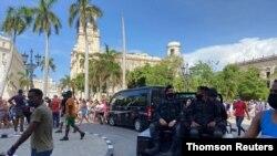 La policía conduce cerca de personas durante las protestas en contra y en apoyo al gobierno, en La Habana.