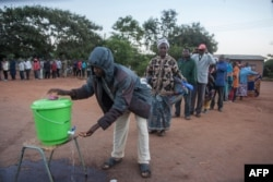 FILE - People queue to wash their hands as a preventive measure against the spread of the COVID-19 coronavirus before they can queue again to vote at a polling station in Lilongwe, June 23, 2020.