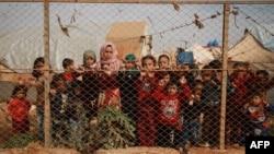 Anak-anak pengungsi Suriah berdiri di balik pagar di luar tenda penampungan mereka di desa Kafr Lusin, kawasan utara pedesaan Idlib, dekat perbatasan Suriah-Turki, 22 Oktober 2019. (Foto: dok).