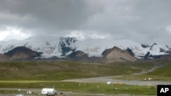 """青海省果洛藏族自治州境內藏族""""四大神山""""之一""""阿尼瑪卿山""""腳下的朝拜者帳篷。"""