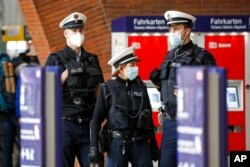 Police with face masks control the coronavirus orders at the train station in Cologne, Germany, Oct. 15, 2020. The city exceeded the important warning level of 50 new infections per 100,000 inhabitants in seven days.
